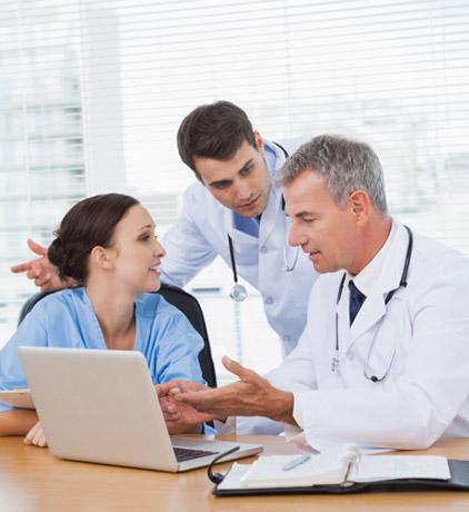 Doutores  atendendo uma consulta online num portatil.